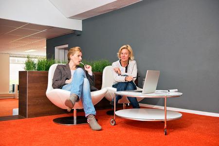Deux collègues de discuter d'un projet dans un bureau informel, avec un ordinateur portable, les notes et les deux femmes en tenue décontractée Banque d'images