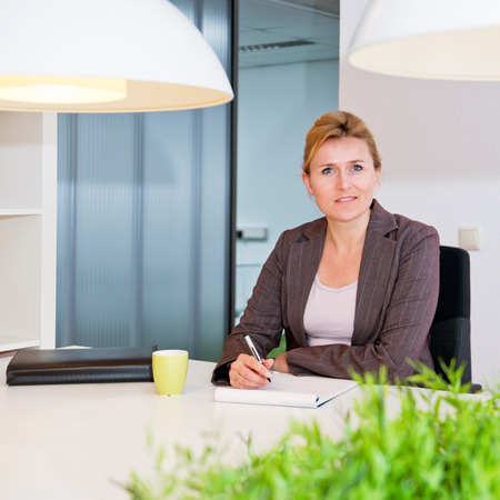 open floor plan: Senior business woman sitting at a desk in a stylish office with an open floor plan Stock Photo