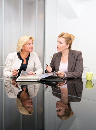 discussing: Two senior business women meeting in a modern meeting room