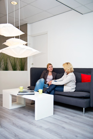 two women talking: Two business women talking on a couch in a corporate waiting area before a sales pitch - creative industry