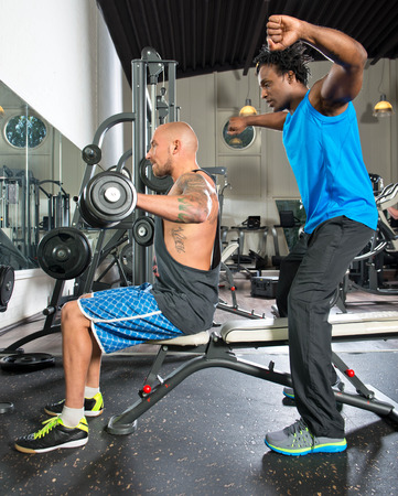 weight machine: Personal trainer motivating a student working out in a gym, lifting dumbbells