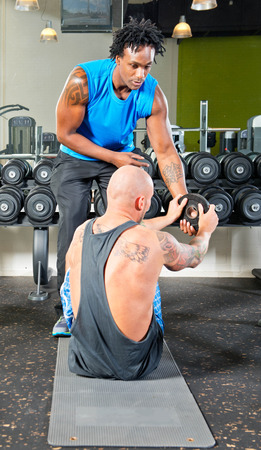 tatoos: Personal trainer at work with a pupil, helping him in passing weights during a situps exercise
