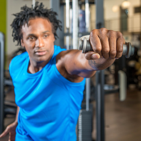 Black man working out in a gym, pulling weights on a machine and training his arms