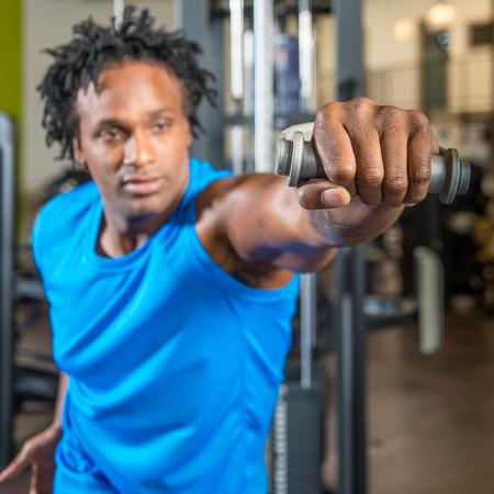man working out: Hombre negro que trabaja en un gimnasio, tirando de pesos en una m�quina y la formaci�n de los brazos