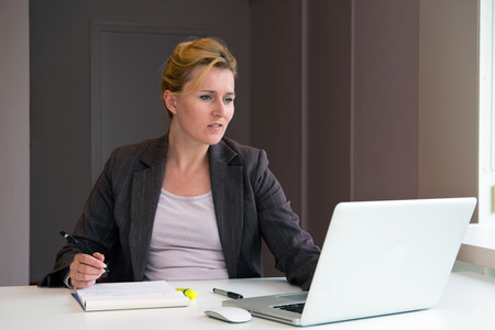Business woman taking notes from her laptop, sitting behind a desk in an office with earthy colors photo