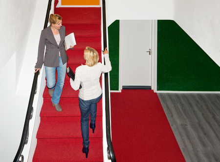 Two business women meeting eachother on a red carpeted stair case in a modern office building photo