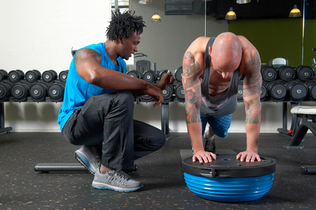 stamina: A man assisted by his personal trainer exercising in a gym