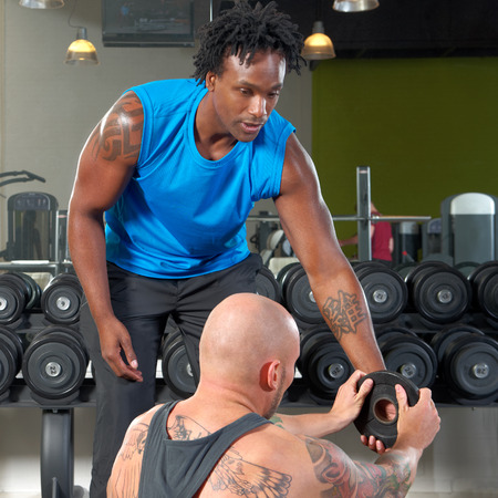 shaved head: A man assisted by his personal trainer exercising in a gym