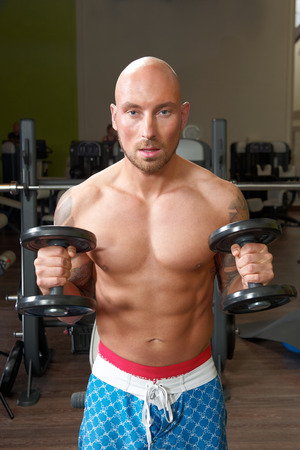 shaved head: Portrait of a man exercising in a gym Stock Photo