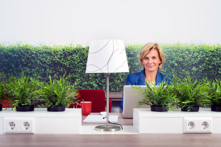 environmentalists: Portrait of confident female environmentalist sitting at desk in office