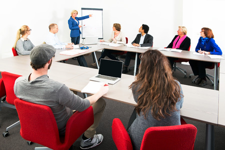 association: Several businesspeople meeting in a spaceous meeting room for a presentation