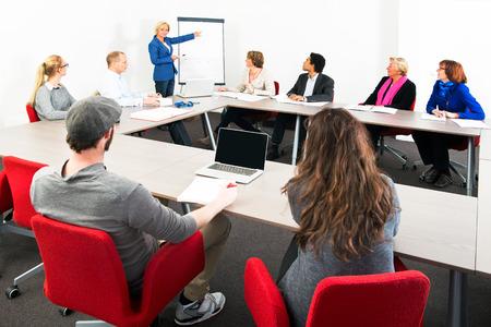 Verschillende ondernemers bijeenkomst in een spaceous vergaderzaal voor een presentatie