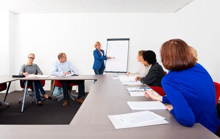 Plenaire vergadering van een klein bedrijf, verzameld in een vergaderruimte rond een flip-over Stockfoto