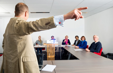 entrepreneurs: Male entrepreneur giving presentation to colleagues in conference room, focus on the pointing hand
