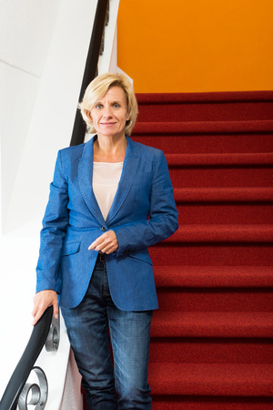 entrepreneurial: Portrait of confident businesswoman standing on steps in office