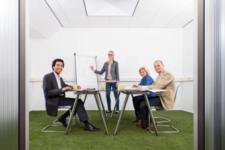 sustentabilidad: Reunión de la pequeña empresa, con cuatro personas en un pequeño y elegante sala de conferencias con la hierba en el suelo, discutir la estrategia, el crecimiento, la sostenibilidad y el medio ambiente inpact de los negocios, Foto de archivo