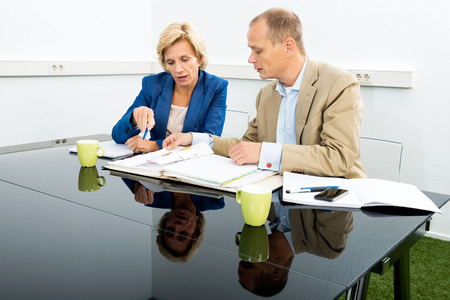environmentalists: Male and female environmentalists discussing over documents at desk in office Stock Photo