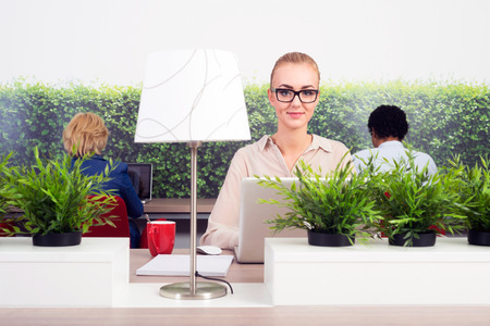 traineeship: Portrait of smiling business woman working in a green office, sitting at a hot desk, with two others in adjacent seats