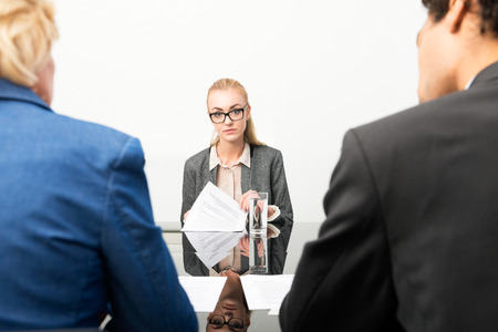 traineeship: Applicant facing the human resource panel during her job interview, nervously flipping through her resume