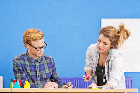 brain storming: Two designers at work, co-designing a product, with markers in various colors in a colorful office with a white board and a blue wall
