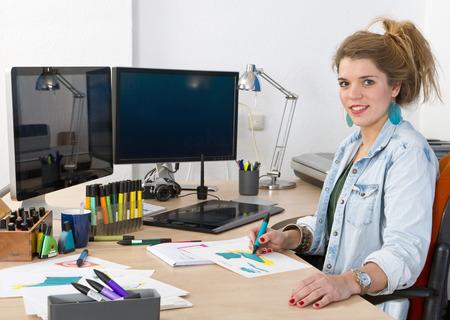 Giovane designer di prodotto disegno schizzi di prodotto alla sua scrivania Archivio Fotografico - 24702298