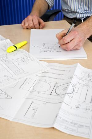 El hombre, tomando notas en un bloque de nota con varios dibujos técnicos de moho en frente de él. Un Ingeniero de Diseño Industrial en el trabajo