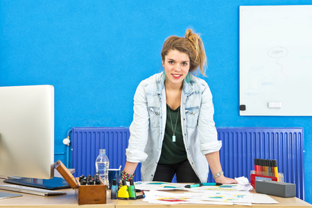 glassboard: Young product designer standing behind her desk, leaning over several product sketches, smiling at the camera