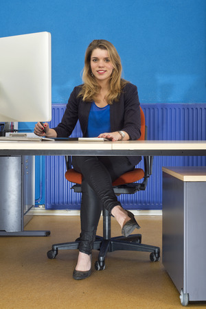 ergonomics: Young pretty woman sitting behind a big computer screen at her desk, using a sketch tablet in an office with a blue wall