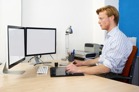 Computer Aided Design (CAD) Engineer at work behind two large monotors, using a tablet and graphic pen in product development