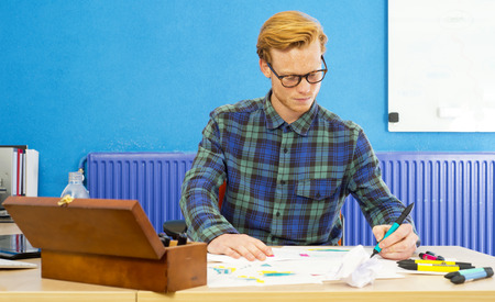 Young cartoonist at work, coloring sketches and drawings behind his desk photo