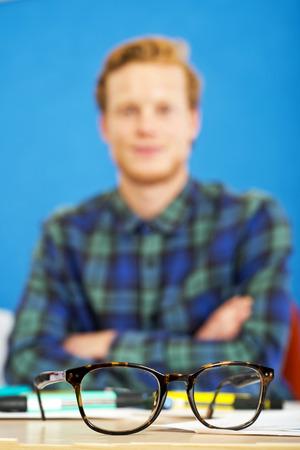rimmed: Un par de gafas de montura de cuerno en el escritorio de un dise�ador gr�fico. Poca profundidad de campo, se centran en las gafas.