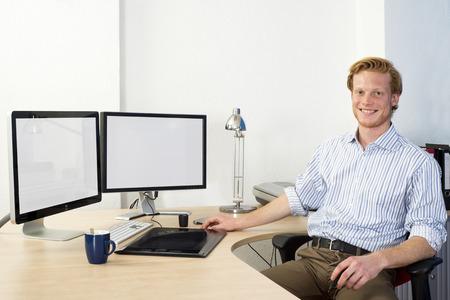 젊은 디자인 엔지니어, 워크 스테이션 웃는 자신의 책상 뒤에 앉아 자신있게 강력한 컴퓨터 지원 설계 (CAD)를 사용하여
