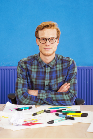 felt tip: Cartoonist, sitting with his arms crossed behind his desk in front of several sketches, drawings and illustrations, littered with felt tip markers Stock Photo