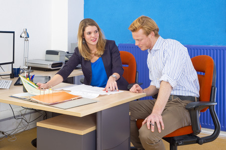 Two coworkers, forming a project team, discussing a design brief and some technical drawings, spred out over a desk in an office Stock Photo - 24921772