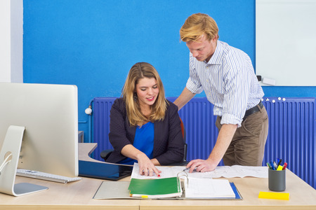 glassboard: Two product engineers discussing technical drawings on a desk in an office