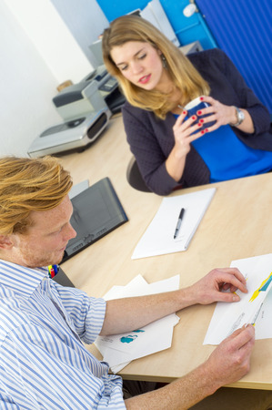evaluating: Young designer showing his work to a female coworker, sitting behind a large desk in a design studio, discussing product ideas and conceptual sketches. Focus on the man in front Stock Photo