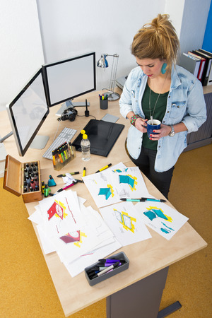 refills: Designer, standing behind her desk in a design studio, reviewing a large variety of conceptual design drawings and sketches Stock Photo
