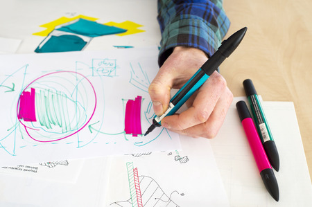 product design: Left handed designer making a rough sketch of a system solution during the product design process