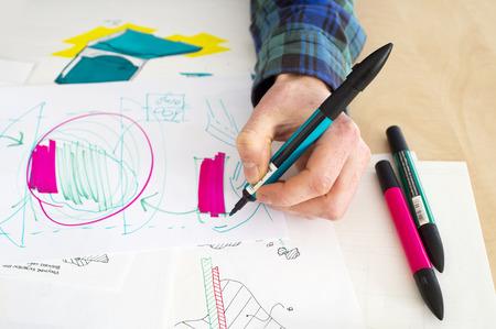 Linkshänder Designer machen eine grobe Skizze einer Systemlösung während des Produktentwicklungsprozesses