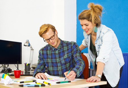 developing: Two creative designers, working on a product innovation, developing ideas and brainstorming together behind a desk in a design studio