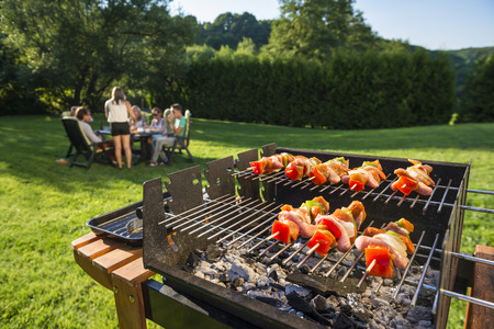 Shlashlick laying on the grill with a group of friends in the background eating and drinking in the late sunny afternoon Stock Photo