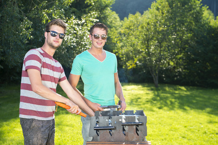 Two men standing around a barbecue on a sunny summer afternoon in a large garden photo