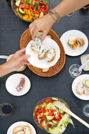Sommer Styled Tisch, mit einer Hand Übergabe eines Platte mit Brot und Französisch Blauschimmelkäse zu einem anderen Gast zum Abendessen, von oben gesehen