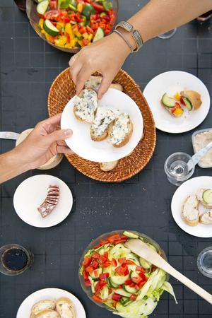 essen und trinken: Sommer Styled Tisch, mit einer Hand �bergabe eines Platte mit Brot und Franz�sisch Blauschimmelk�se zu einem anderen Gast zum Abendessen, von oben gesehen