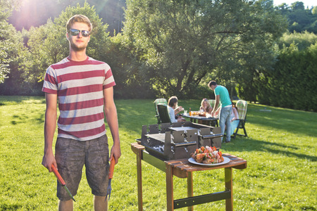 barbecue party: Man, posing next to a barbecue, hoding a fork and pliers, with a group of friends sitting around a picknick table in the background on a sunny summer afternoon. Stock Photo
