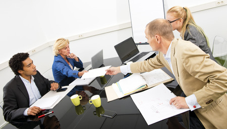 hectic: Four coworkers working frantically during a hectic project team meeting, finding solutions, and solving problems Stock Photo