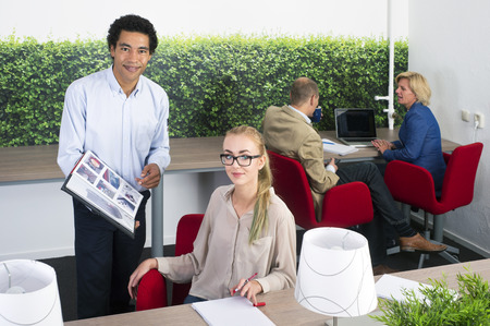 constructive: Coworkers discussing a project in an open office space Stock Photo