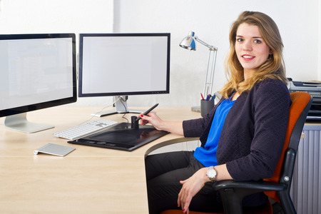 Young CAD engineer, using a powerful dual screen  workstation sitting confidently behind his desk, smiling photo