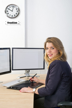 graphic tablet: designer working towards a deadline, using a graphic tablet and a dual monitor computer. The clock on the wall symbolises the deadline