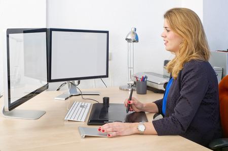 Jeune femme assise derrière un grand bureau et un ordinateur à double écran, à l'aide d'une tablette graphique et le pad de piste lors de travaux de conception
